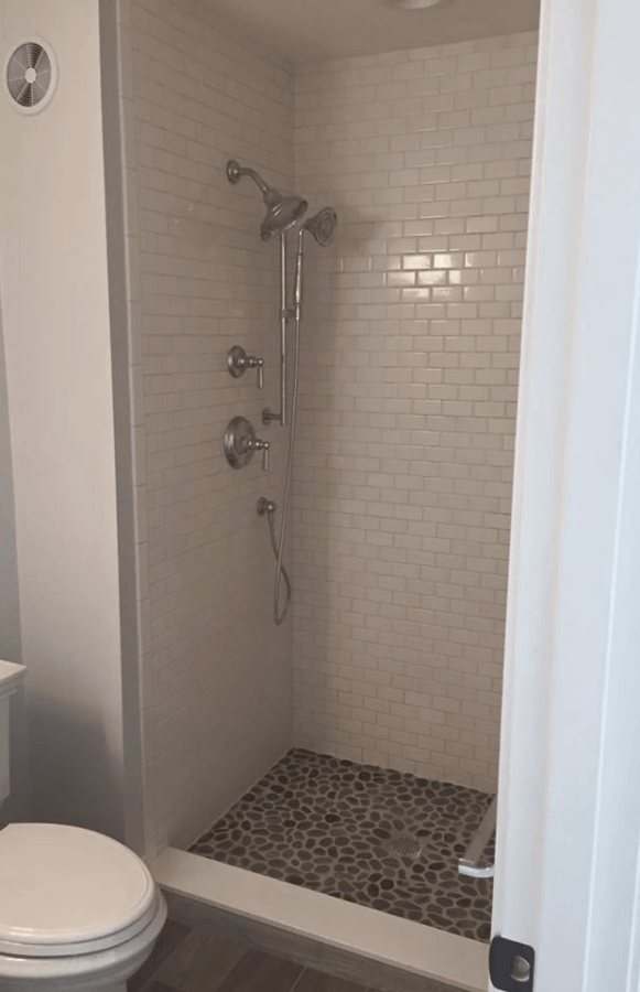 Spa-like bathroom renovation | wood-grain tile | pebble shower floor